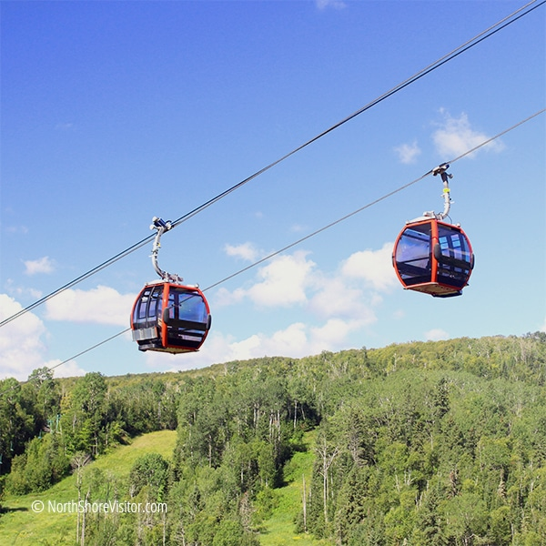 two red gondolas passing each other over poplar river valley at lutsen mountains