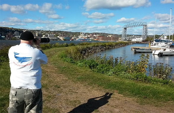 man in whale watching t-shirt with binoculars looking for whale in duluth