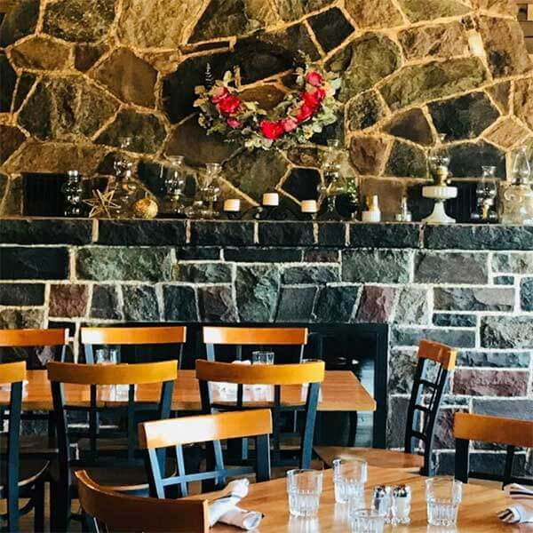 stone fireplace and tables at cascade restaurant overlooking lake superior