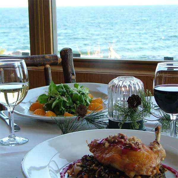 composed citrus spinach salad and chicken wild rice entree with wine at table on edge of lake superior
