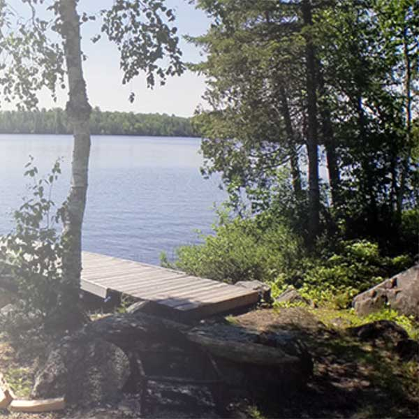 wooden dock and summer trees on poplar lake gunflint trail
