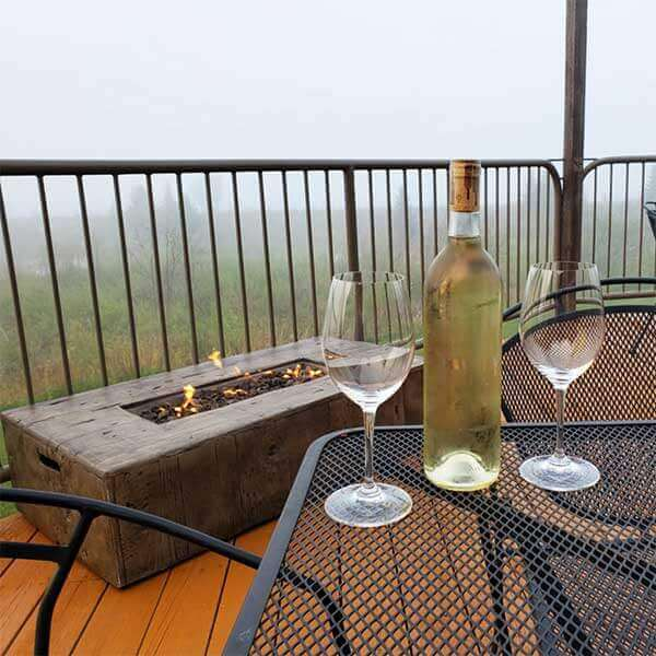 bottle of white wine on bistro table with deck fireplace overlooking lake superior in two harbors
