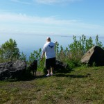 man in whale watching t-shirt and lab on lake superior shore