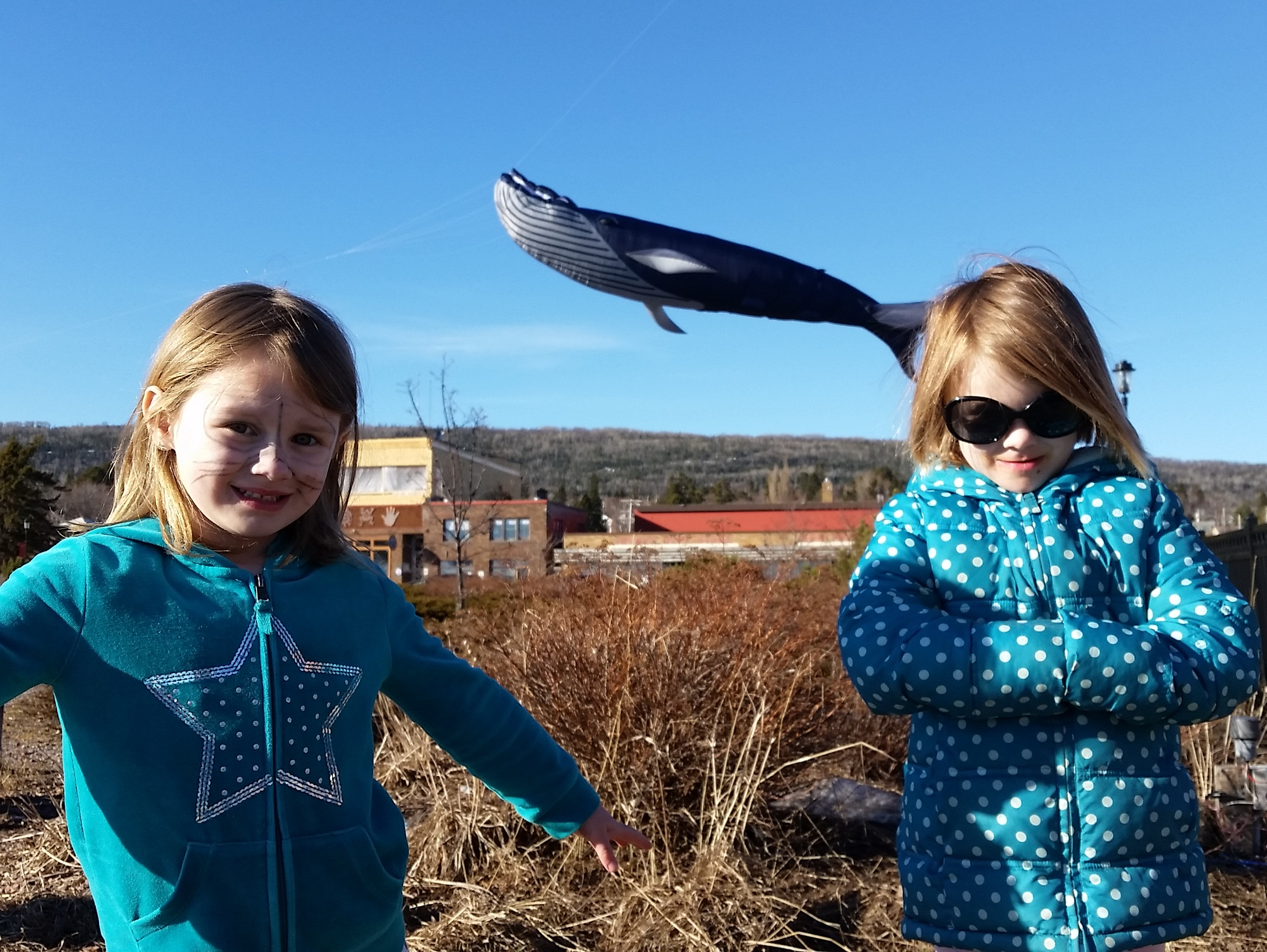 two girls in polka dot turquoise don't realize a whale is passing by