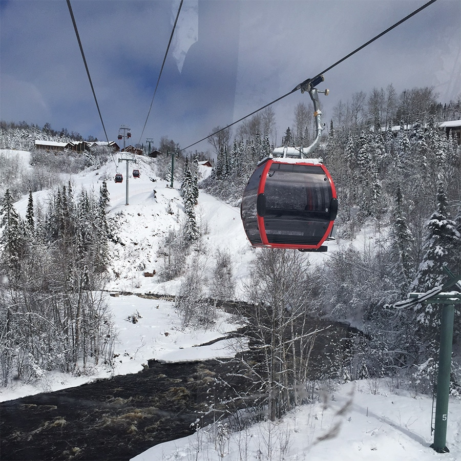 red gondola passes over snowy river up toward chalet