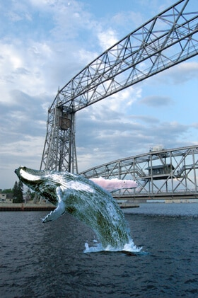 whale jumping in front of aerial lift bridge