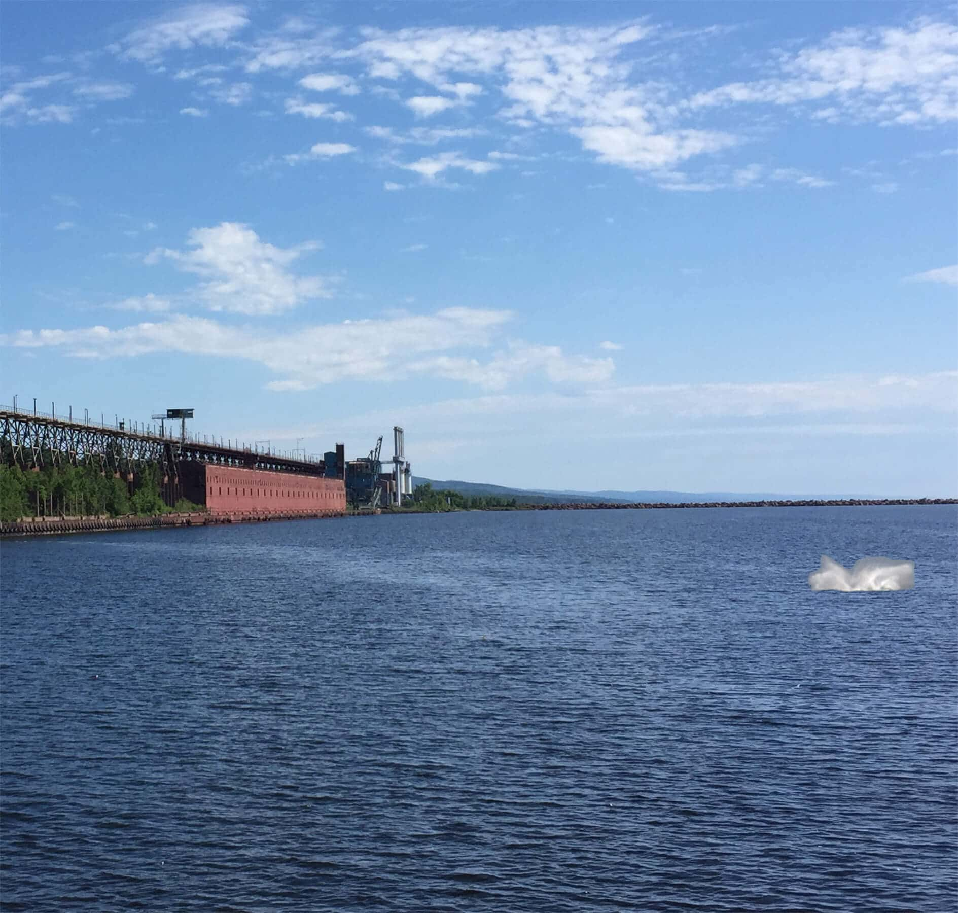 splash from a whale on lake superior with taconite harbor in the background