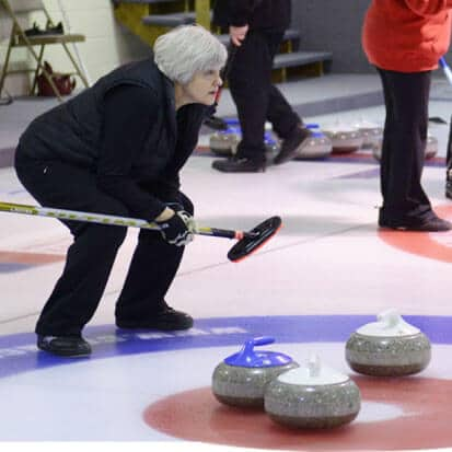 female curler with broom and stone on rink in grand marais