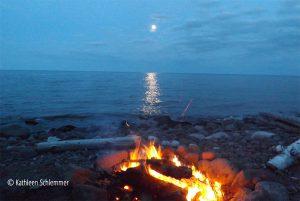 Moonlight and bonfires on a cobblestone beach