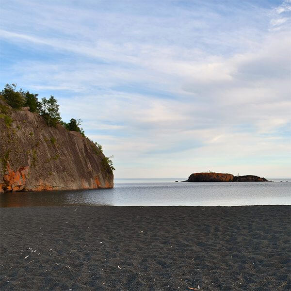 black beach and cliff on lake superior with island