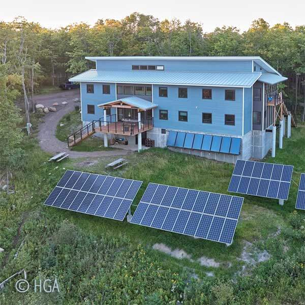 solar panels and exterior of wolf ridge learning center set on a hillside near little marais mn
