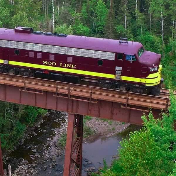 north shore scenic railroad train crossing trestle on lake superior river