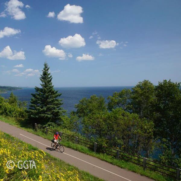 bike rider on gitch gami bike trail along shore of Lake Superior between gooseberry falls and split rock lighthouose