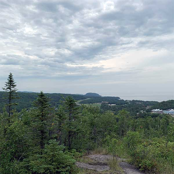 lake superior with palisade head in the distance and the descending hill of the scenic overlook in the foreground