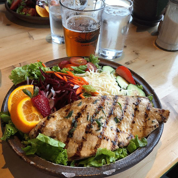 fish and salad with a drink at angry trout cafe