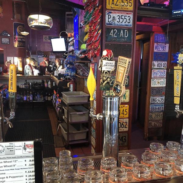 Landing Sports Bar guests and glasses at bar