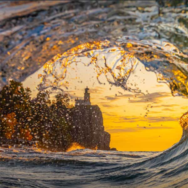 split rock lighthouse through the curl of a wave photo by christian dalbec