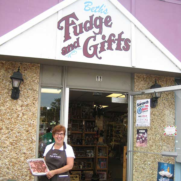 Smiling woman holding pan of fudge at entry to Beth's fudge and gifts