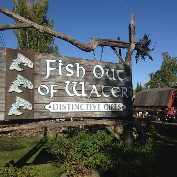 Wooden sign in greenery fish out of water distinctive gifts