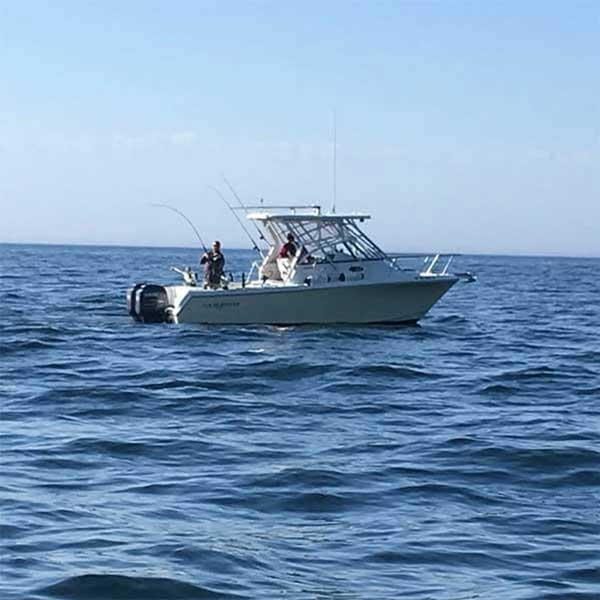 a fisherman catches a fish in lake superior with reel swede charters