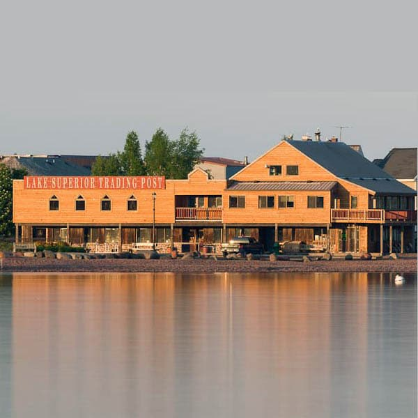 Are the long wooden exterior and balconies of the Lake superior trading Post from across the Grand Marais Harbor