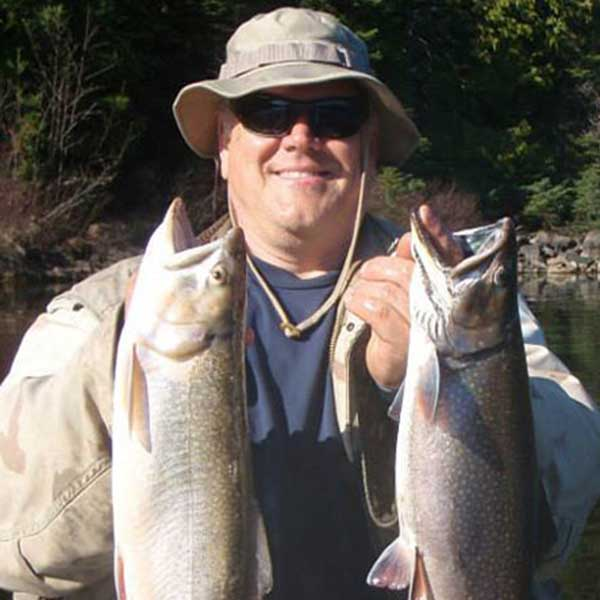a fisherman with two nice trout on a trip with little vinces guide service