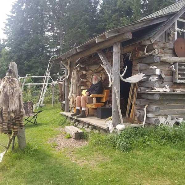 Bearded man sitting on porch of log runningen fur store