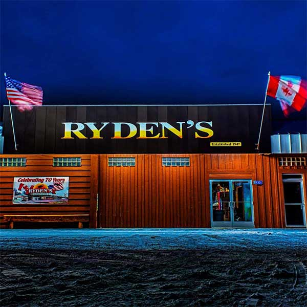 American and Canadian flag fluttering on the outside of Ryden's border store