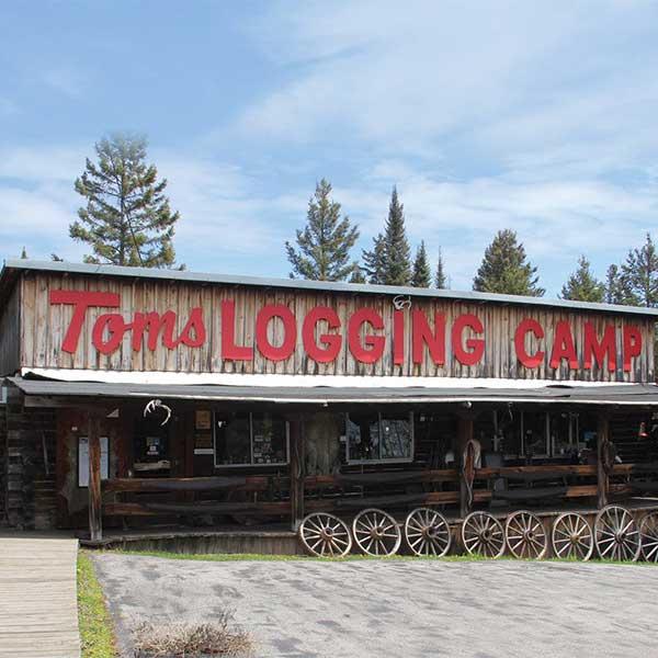Red lettering along wooden building Tom's logging Camp