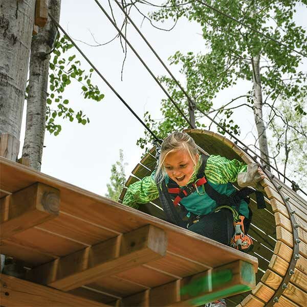 girl climbing out of tunnel at north shore adventure park