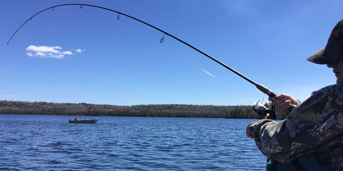 walleye fisherman with bent rod and another fishing boat