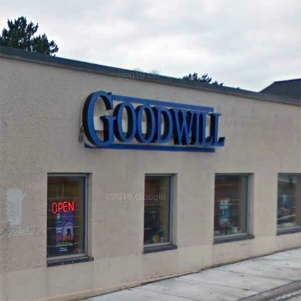 stucco exterior of shop with Goodwill blue sign