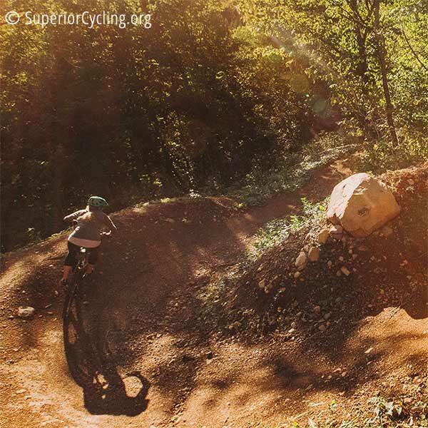 woman mountain bikes through curve on britton peak trail