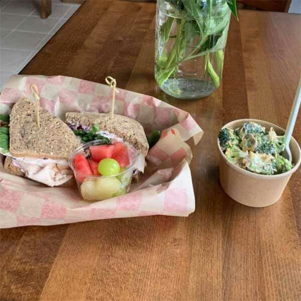 basket with cold sandwich fruit and salad