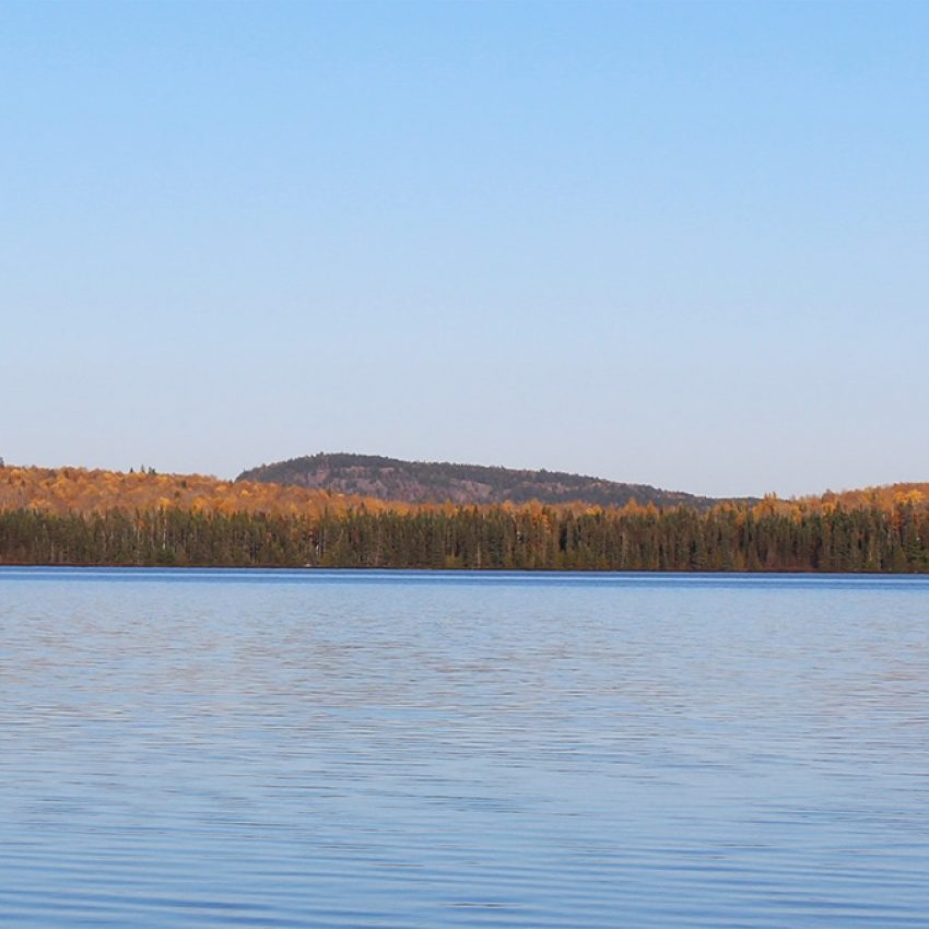 sawtooth mountain rising above inland lake and late season fall colors
