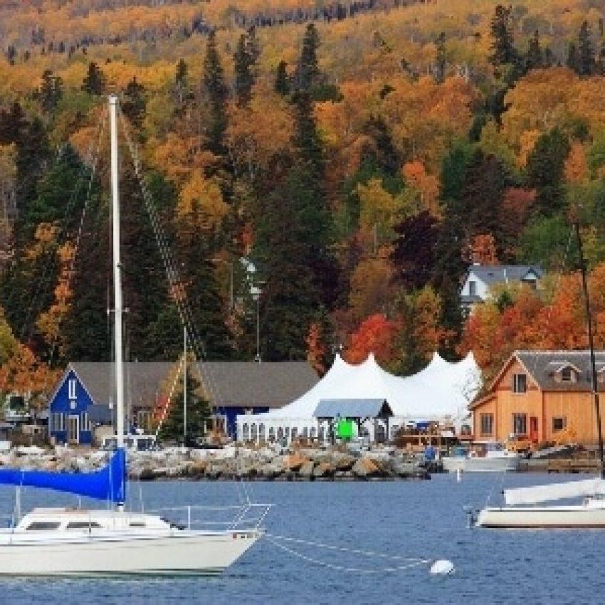 sailboats in the grand marais harbor with north house buildings and white tent