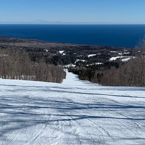 looking down groomed ski run at moose mountain in lutsen with massive blue lake superior