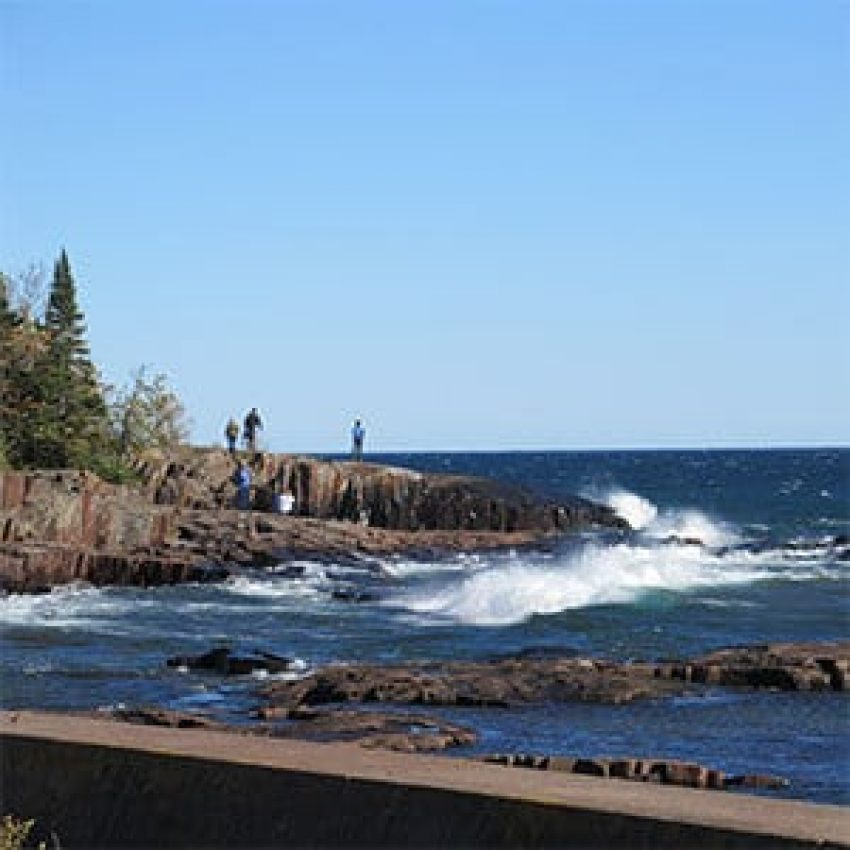 visitors walking the rock points of artist point in grand marais