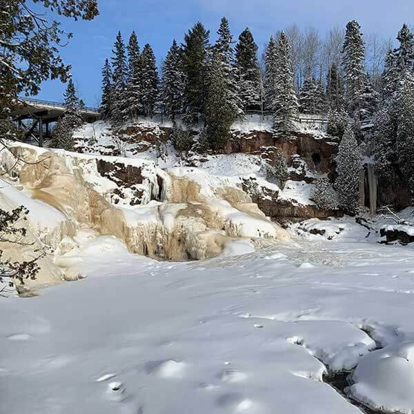 frozen falls and snow covered gooseberry river north shore mn