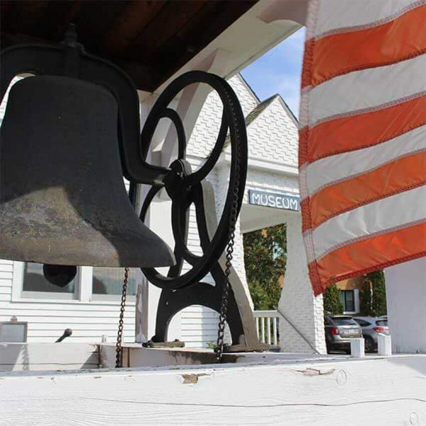 old cast iron bell and flag outside the cook county mn historical society museum