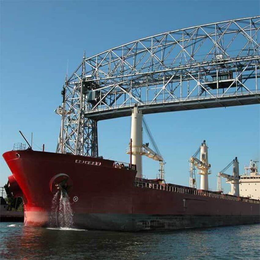 ocean going ship salty sailing under aerial lift bridge through canal in duluth mn
