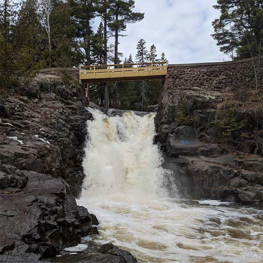 amity creek waterfalls under walking wood bridge