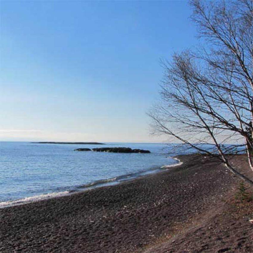 paradise beach cobblestones edge lake superior with a small island off shore