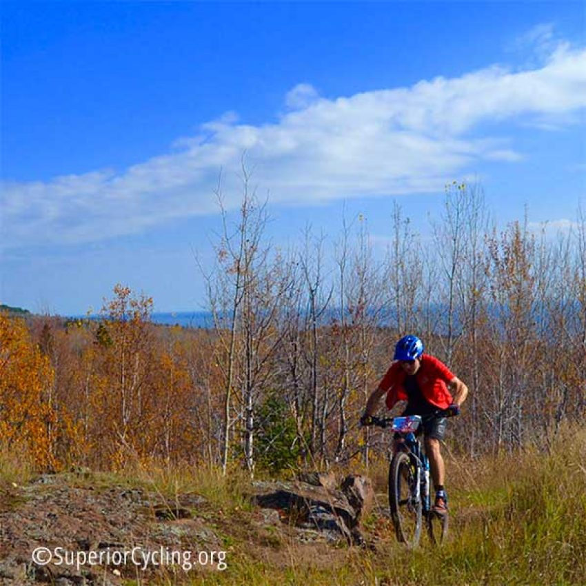 red shirted mountain biker on pincushion trail with lake superior in the background