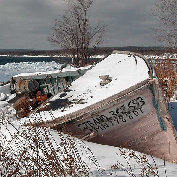 old fishing boat rests in snow along scenic 61 shoreline of lake superior