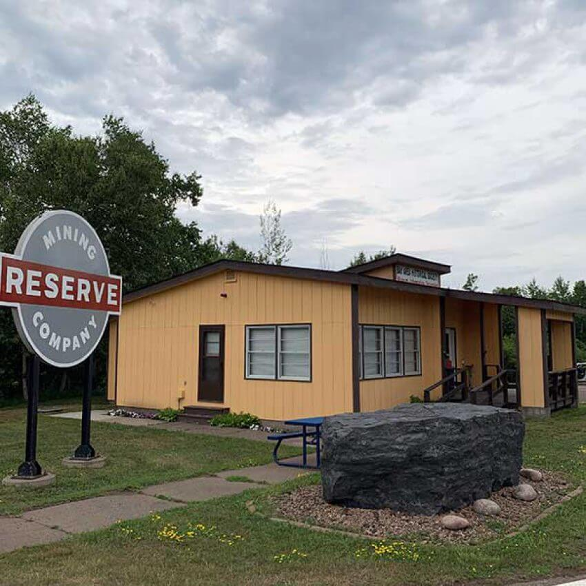 silver bay historical society visitor center with large piece iron ore and reserve mining company sign
