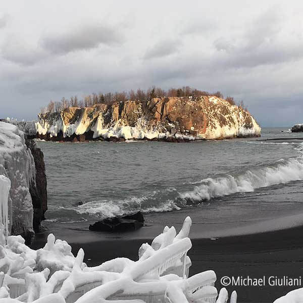 snow covered branches and island at black beach in silver bay mn