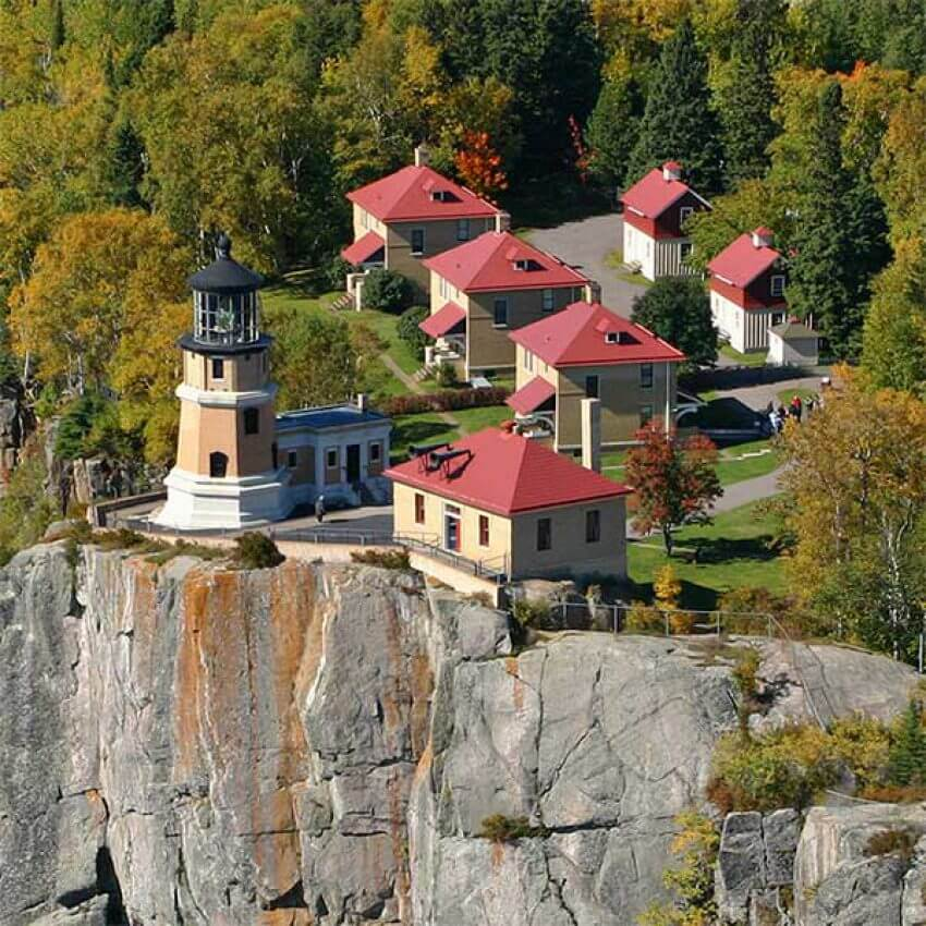 aerial view of split rock lighthouse, fog signal building and lightkeeper's homes on a cliff above lake superior