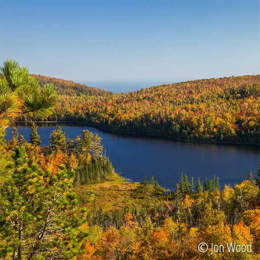 bright fall colors overlooking mic mac lake at tettegouche state park with lake superior in the distance