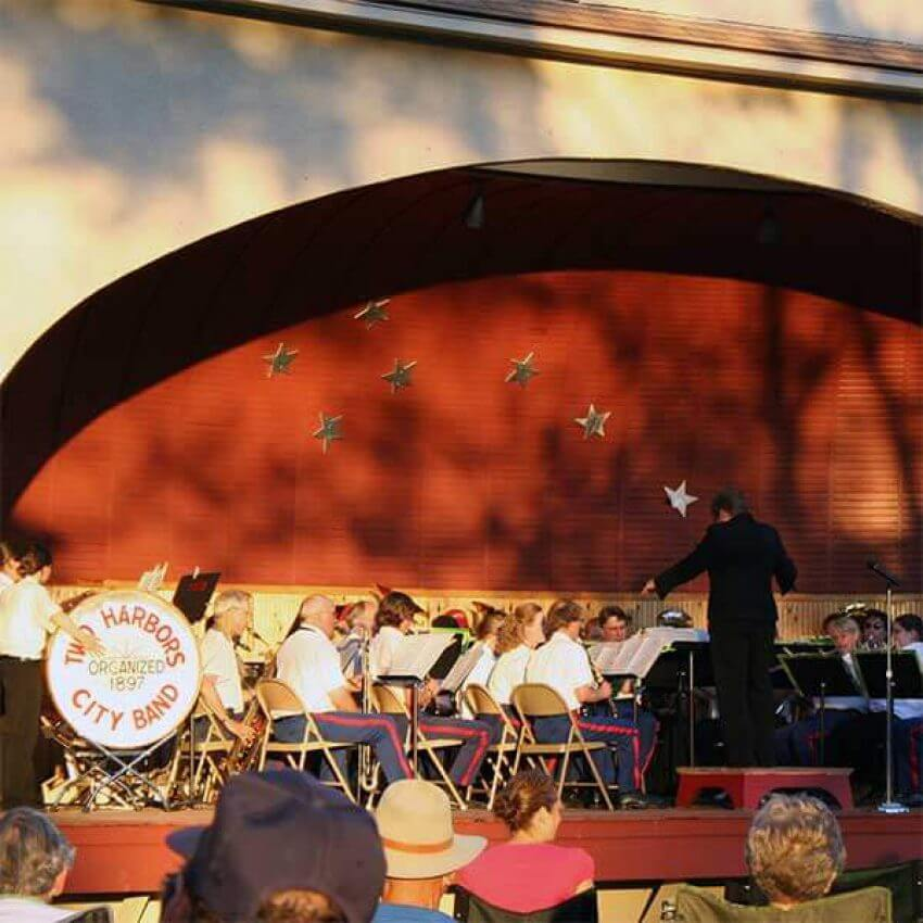 two harbors city band playing in bandshell at thomas owens park